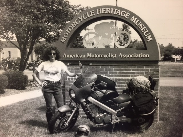 35a07f4d-f59e-416a-be1c-af552c1c5023Ann with packed bike at AMA Museum sign