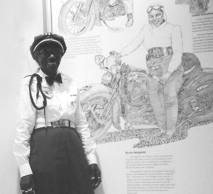 Bessie, age 79, at the motorcycle museum. Background artwork by Paul Jamiol.   <br/>         Photo © by Ann Ferrar. May not be reprinted.