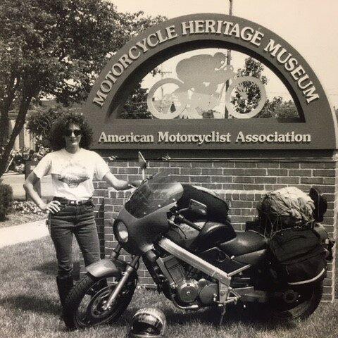 35a07f4d-f59e-416a-be1c-af552c1c5023Ann with packed bike at AMA Museum sign
